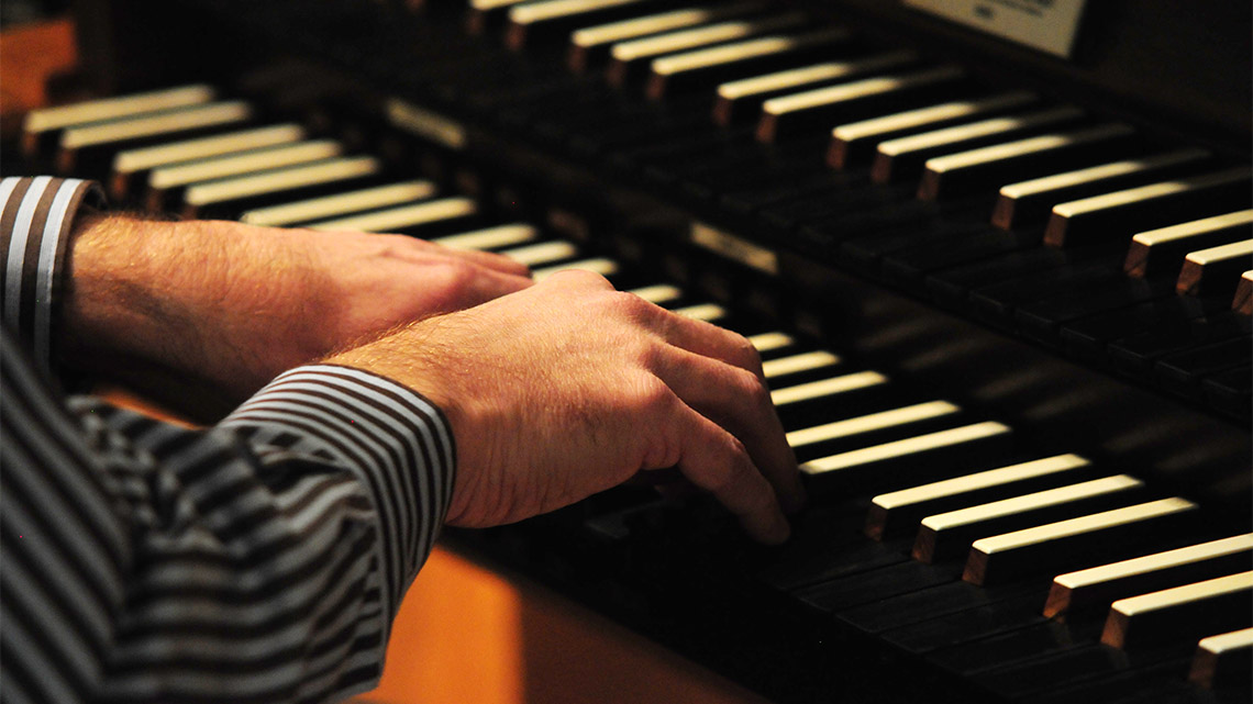 Photo the organist's hands playing the organ.